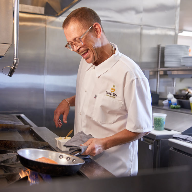 Chef Joel Harrington man in white chef uniform and glasses standing at hot stove holding pan handle with towel and smiling