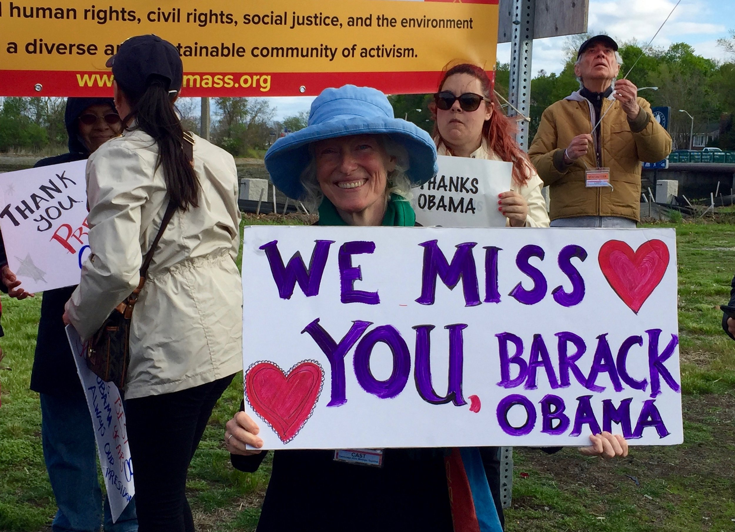 "Eileen Ryan of Watertown, Mass., holds a sign outside the JFK Library in Boston May 7. ""Obama should organize,"" she said, ""and keep inspiring people."" Photo by Rick Holmes"