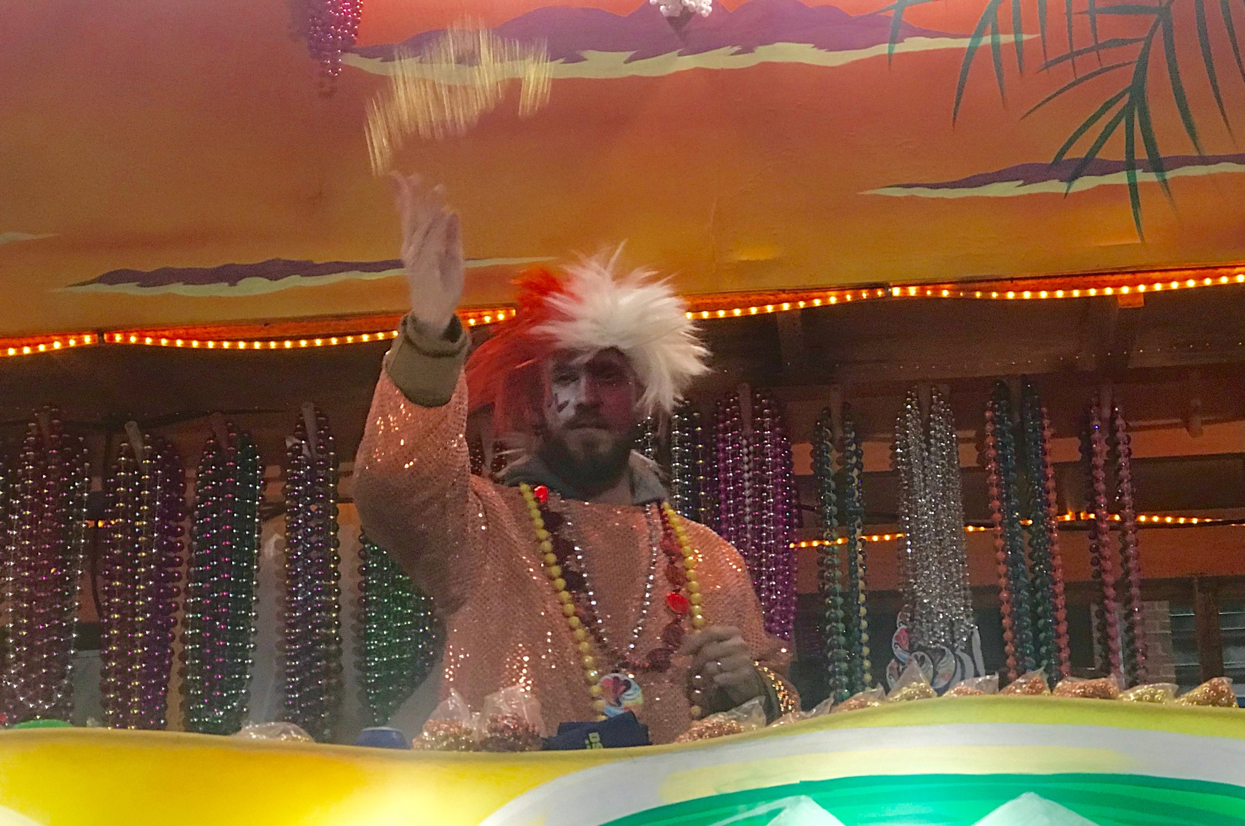 "A member of a Mardi Gras ""krewe"" in Lafayette tosses beads to the crowd in Lafayette."