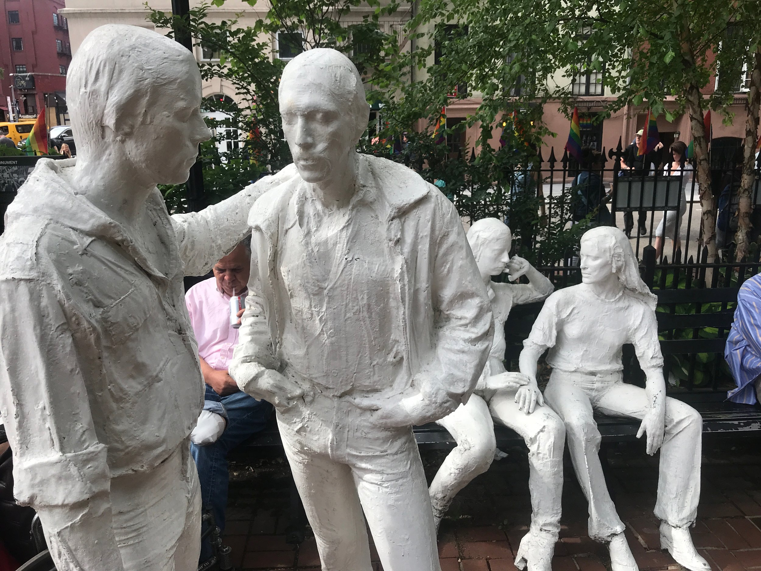 Rainbow flags, sculptures and visitors at the former Sheridan Square in New York's Greenwich Village, which is now part of the Stonewall National Monument.