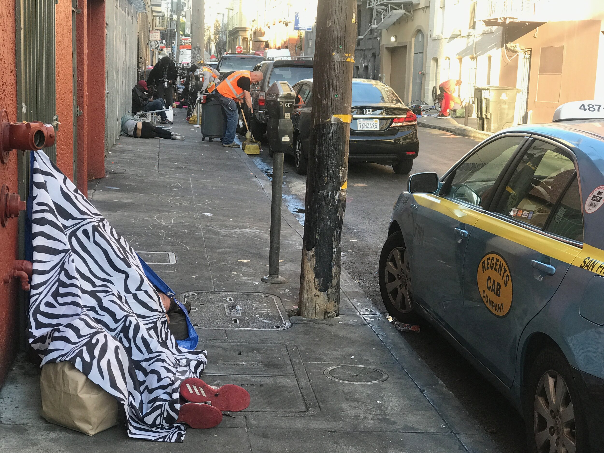 City workers carefully clean up sidewalks in the Tenderloin without disturbing sleeping homeless people. For a century, the Tenderloin has been a haven for the down-and-out.
