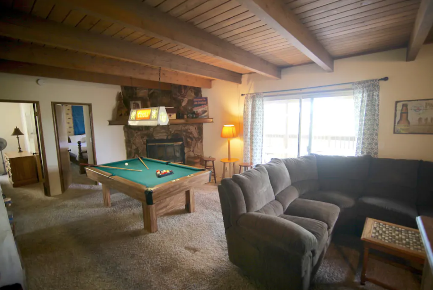 """Game room with pool table and 60"""" flat screen TV."""