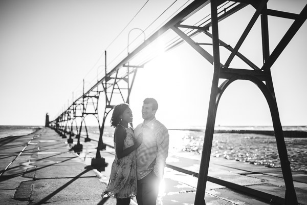couple snuggling on pier at sunset in beautiful light, powerful connection, black and white