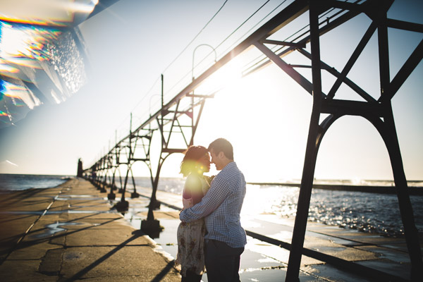 couple touching head to head on pier, backlight, golden hour sun, intimate connection