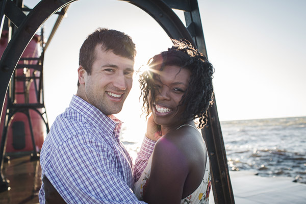 couple smiling at camera on pier