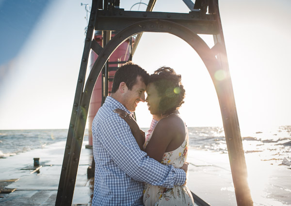 couple touching head to head on pier with light streaming in from behind