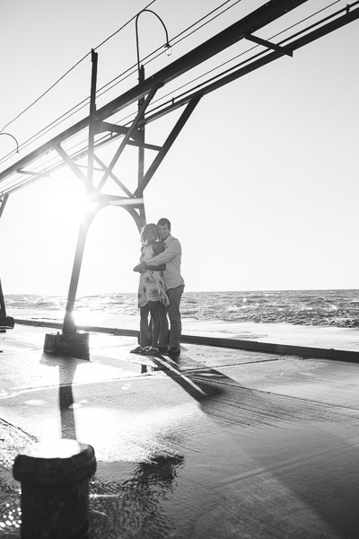 couple wrapped in each others arms on pier, black and white
