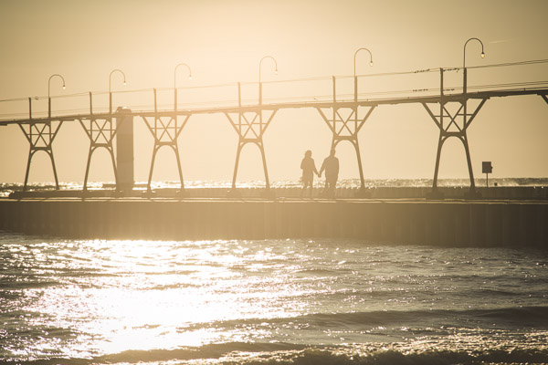 couple walking along golden pier, hand in hand, connected