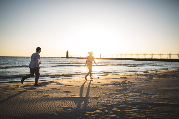 couple chasing each other along the beach in golden sunlight