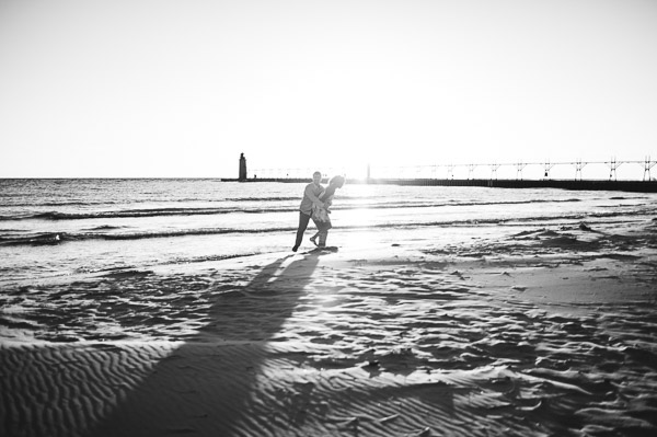 couple embracing on beach in glow of sun, black and white