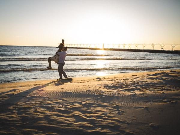 playful interactions between couple on beach in golden sun