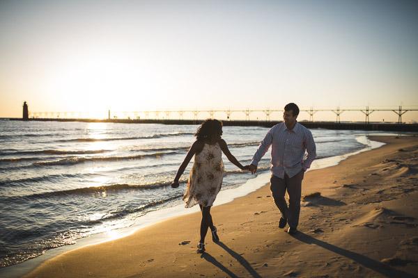 couple running along beach and in hand, golden light