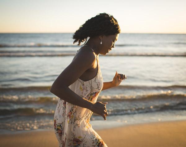 girl running along beachfront in golden light