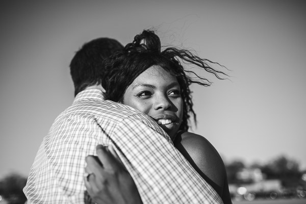 close-up side portrait of woman in embrace with her husband on the beach, black and white