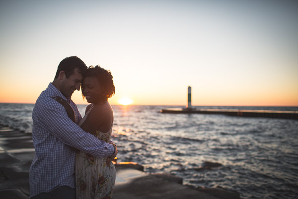 couple touching foreheads on beach with golden sun setting behind