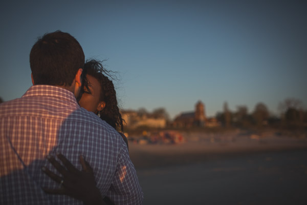 couple kissing on beach, shadow light play, warm embrace, intimate connection