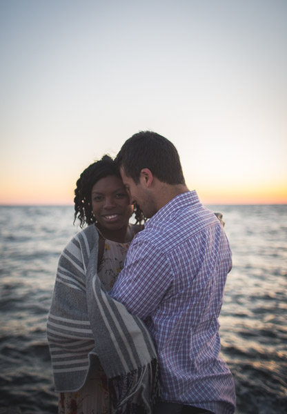couple loving on one another on pier at dusk