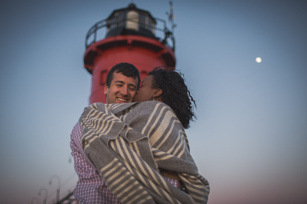 intimate embrace, loving kiss on pier in front of lighthouse with moon shining behind