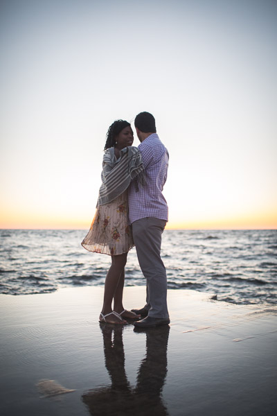 couple embracing on pier as they look out onto the water
