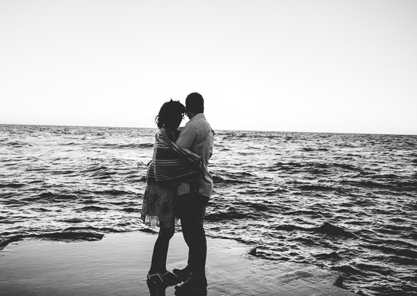 couple in warm embrace as they look out onto the water, black and white