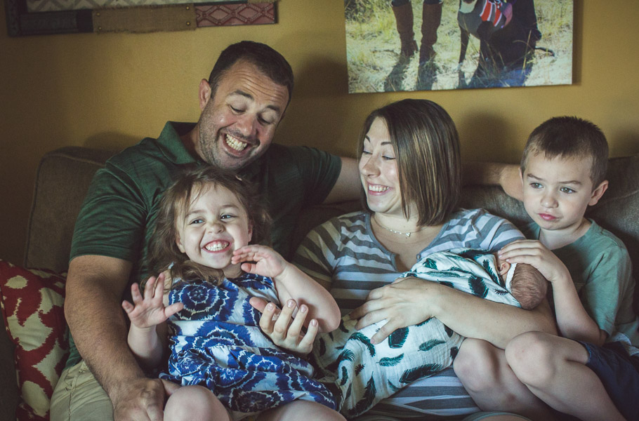 Family giggles full of joy on couch