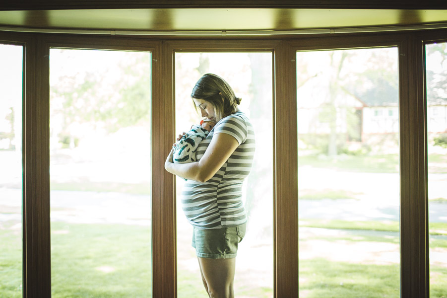 portrait of mother with newborn cradled into her in front of bay windows