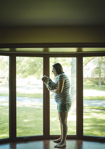 portrait of mother cradling newborn daughter in front of bay windows