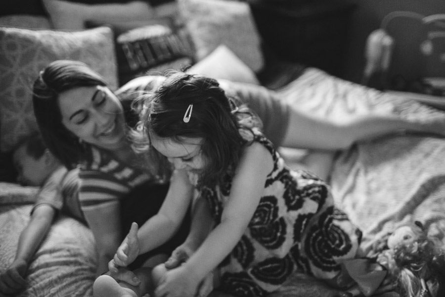 family tickle fight on bed, laughter, joy, connection, black and white