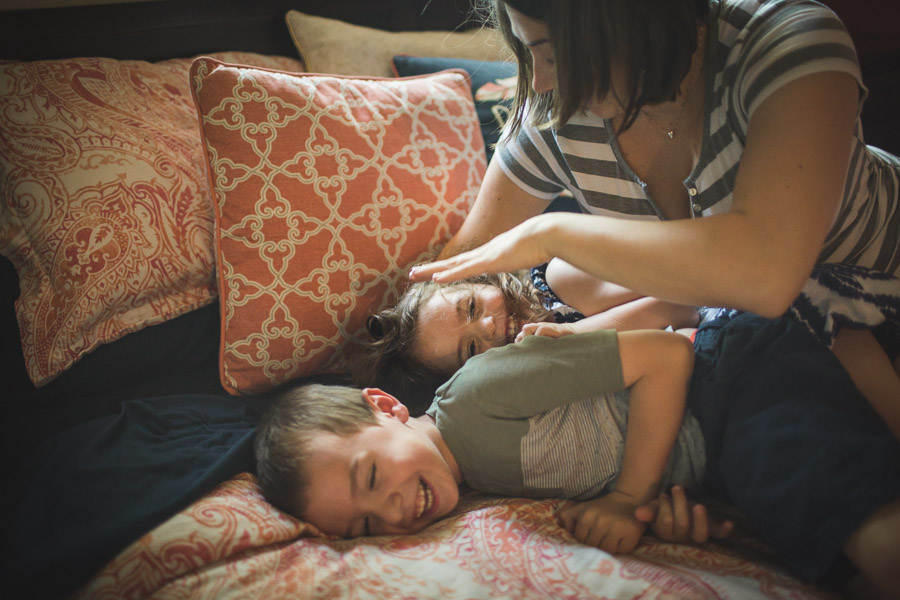 mother ticking children on bed in laughter and joy