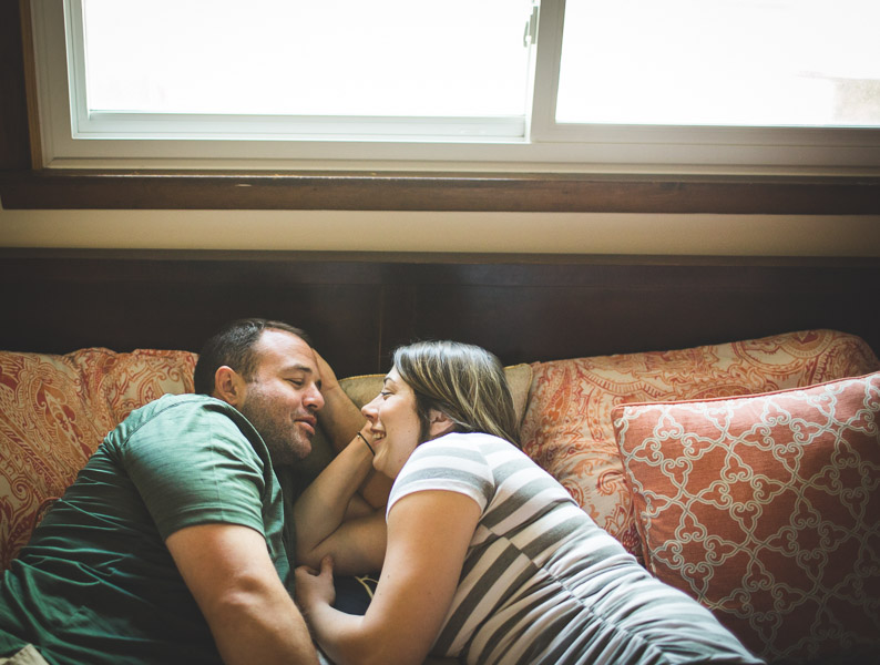 couples snuggling on bed in soft window light