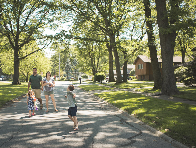 family skipping down street through neighborhood, filled with joy