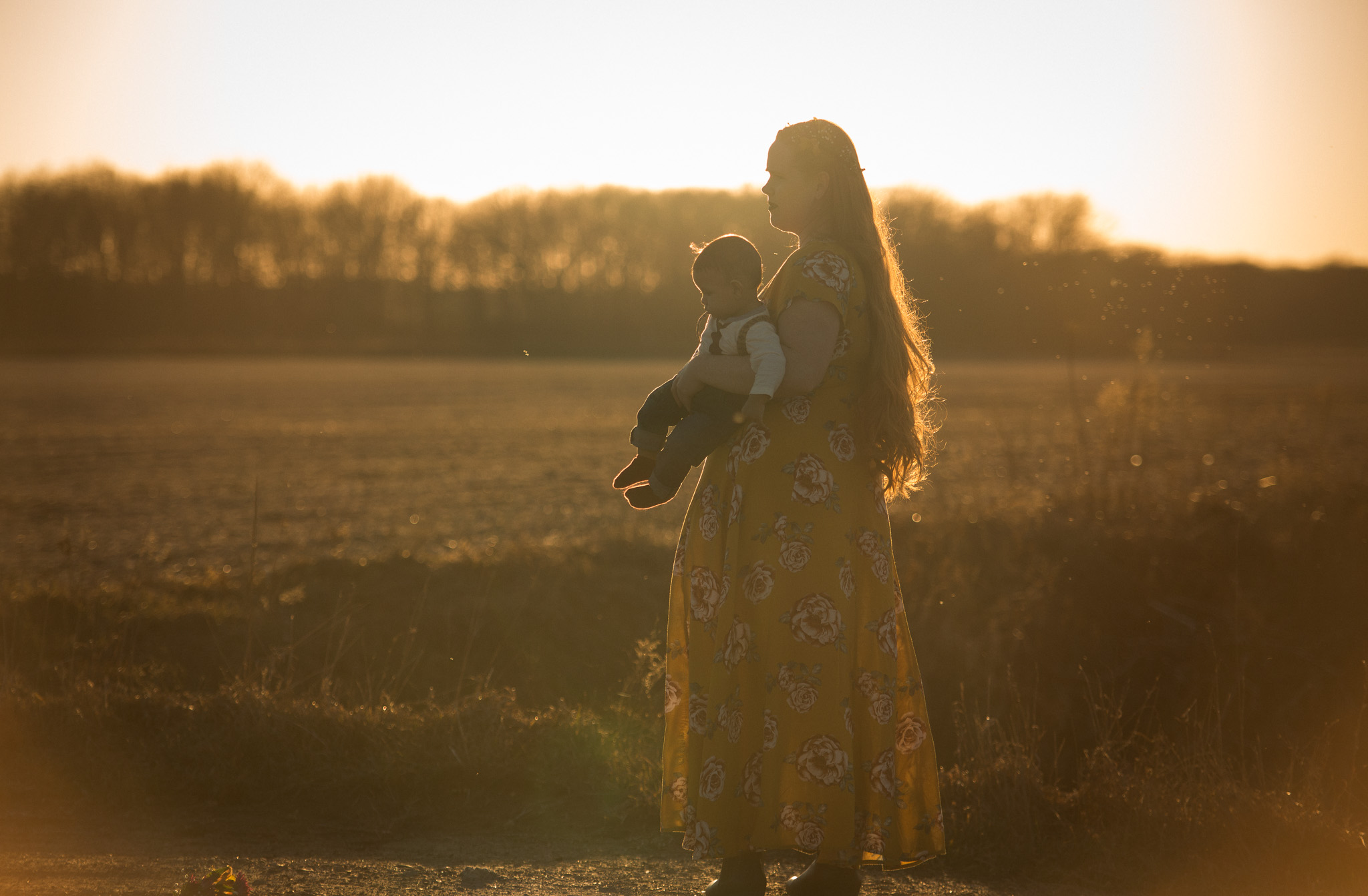 Mother walking in the field carrying her son in the golden sunset