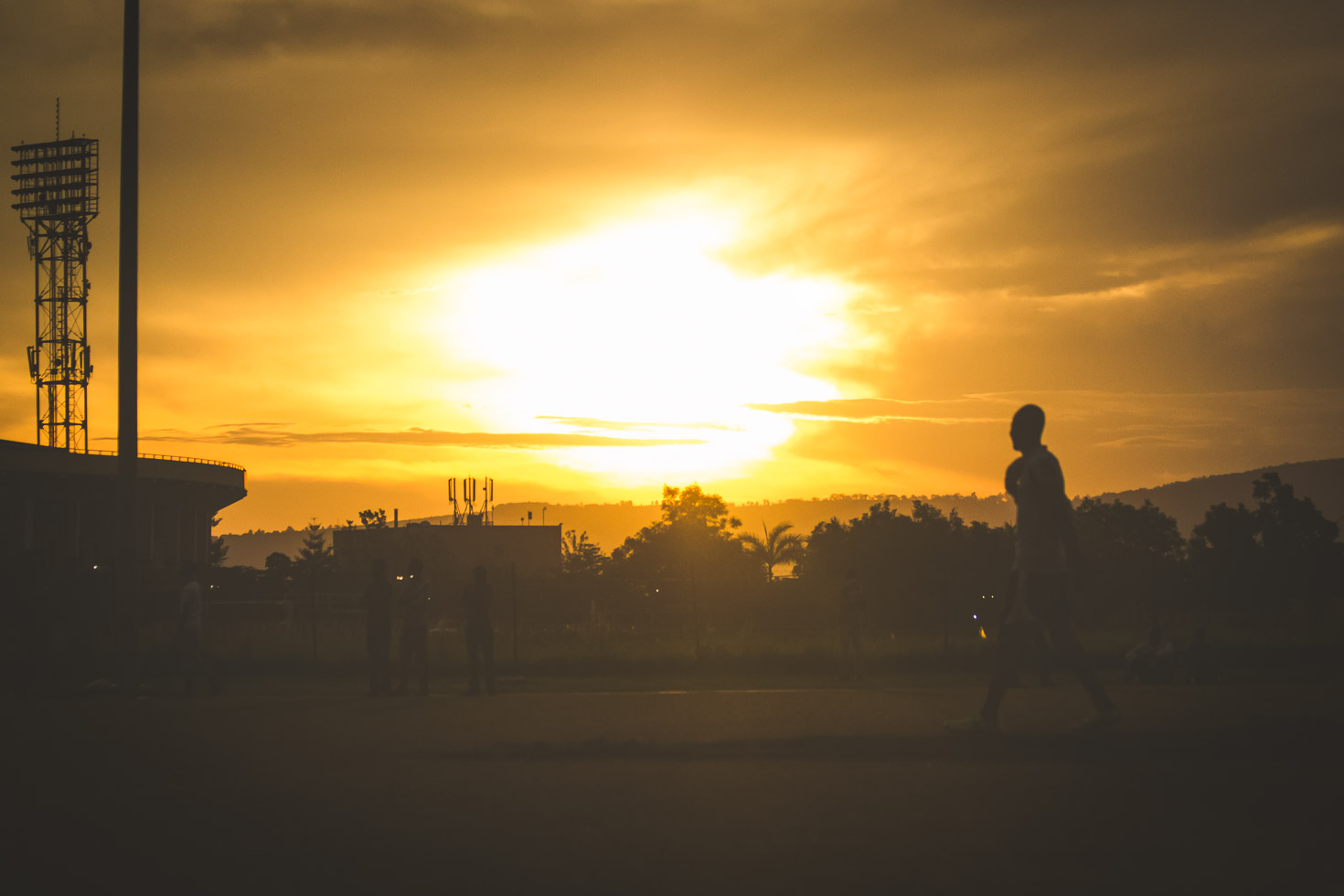 Soccer goalie walking the field with backlight silhouette of sun; Africa, Powerful