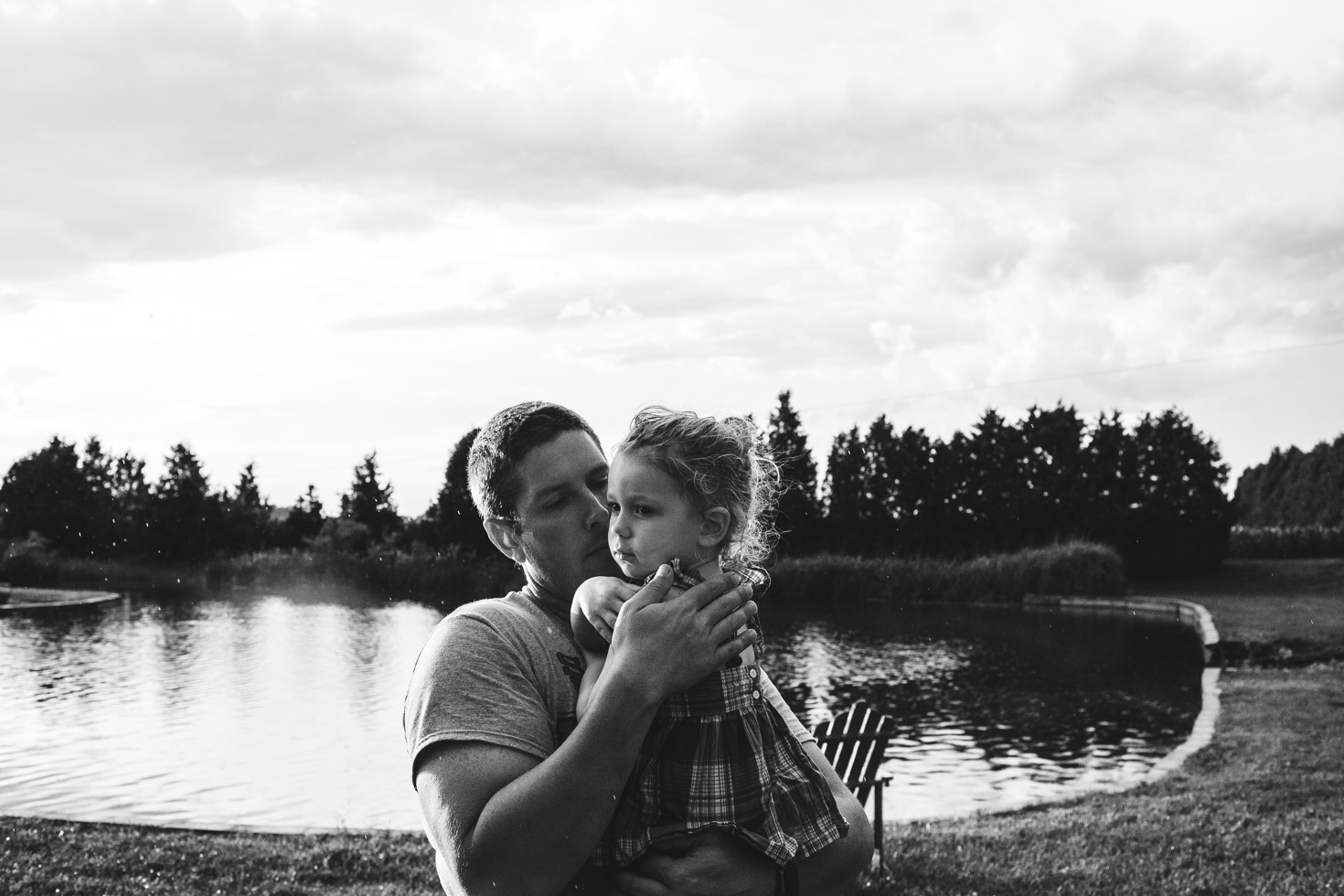Father embracing daughter, country field in front of lake, connection, powerful black and white