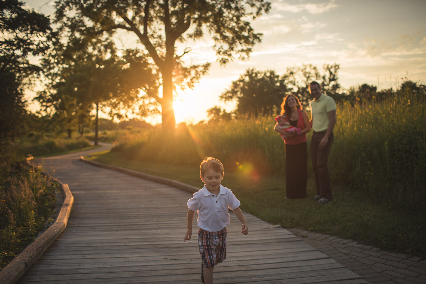 Boy running through golden light with family watching from behind, Coffee Creek Watershed Preserve