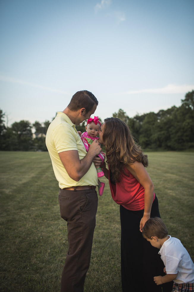 Family connecting over kisses in wide open field