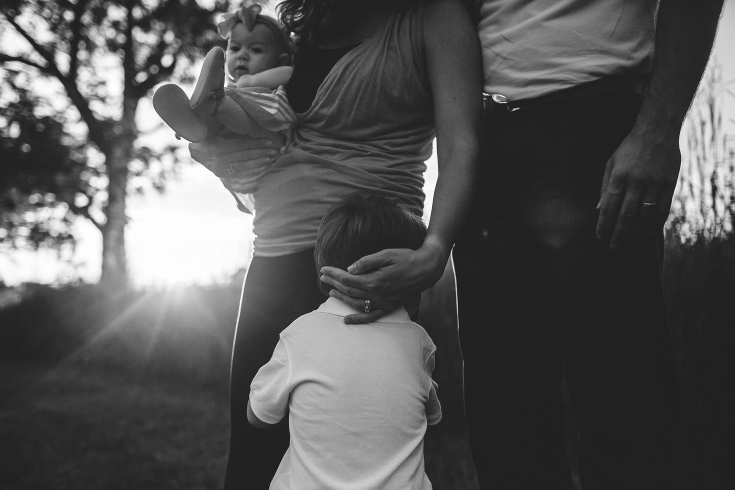 Emotional Family portrait as mother embraces sons head as she holds her daughter, backlight, black and white, documentary style