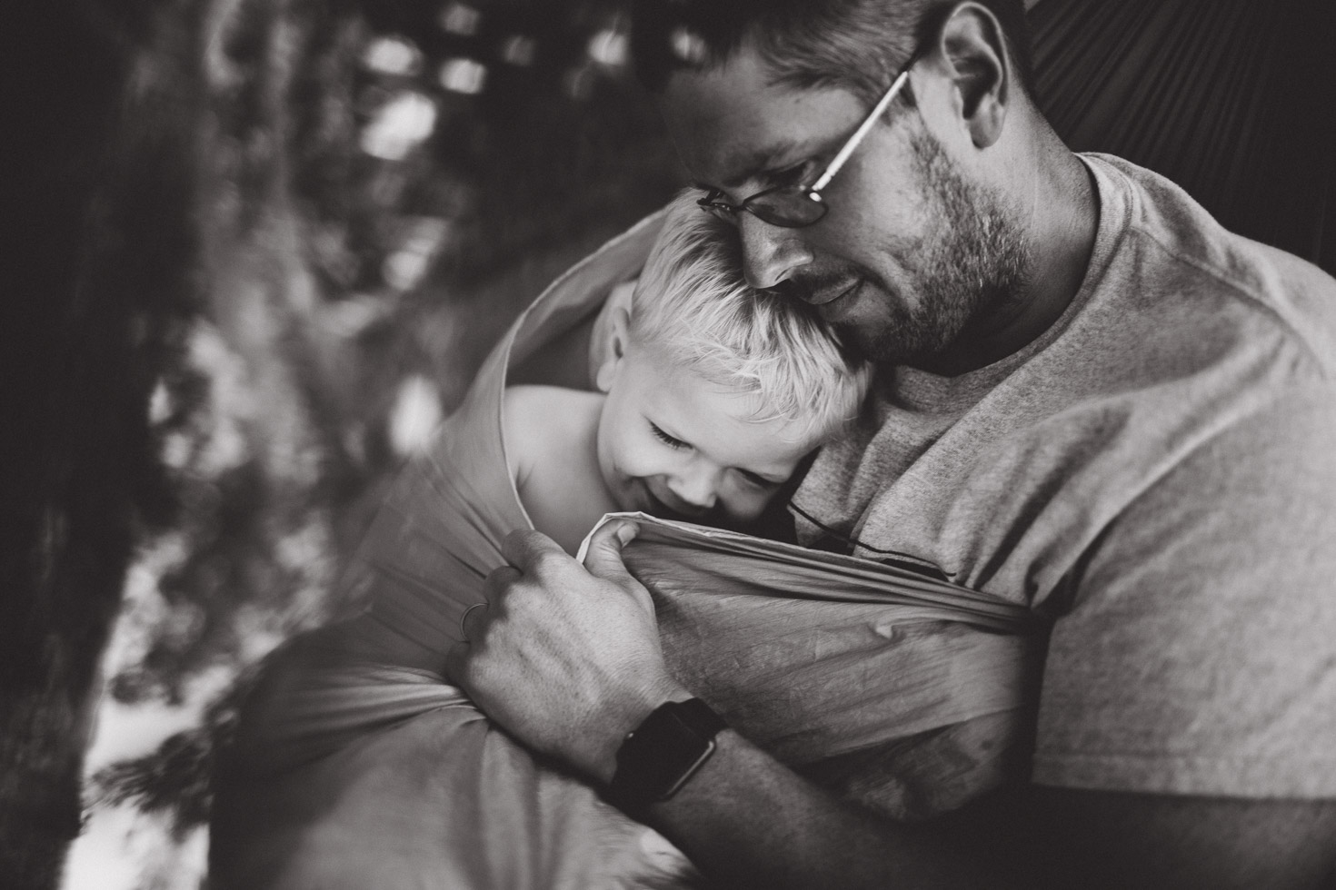 Father embracing son in loving connection in hammock; black and white portrait