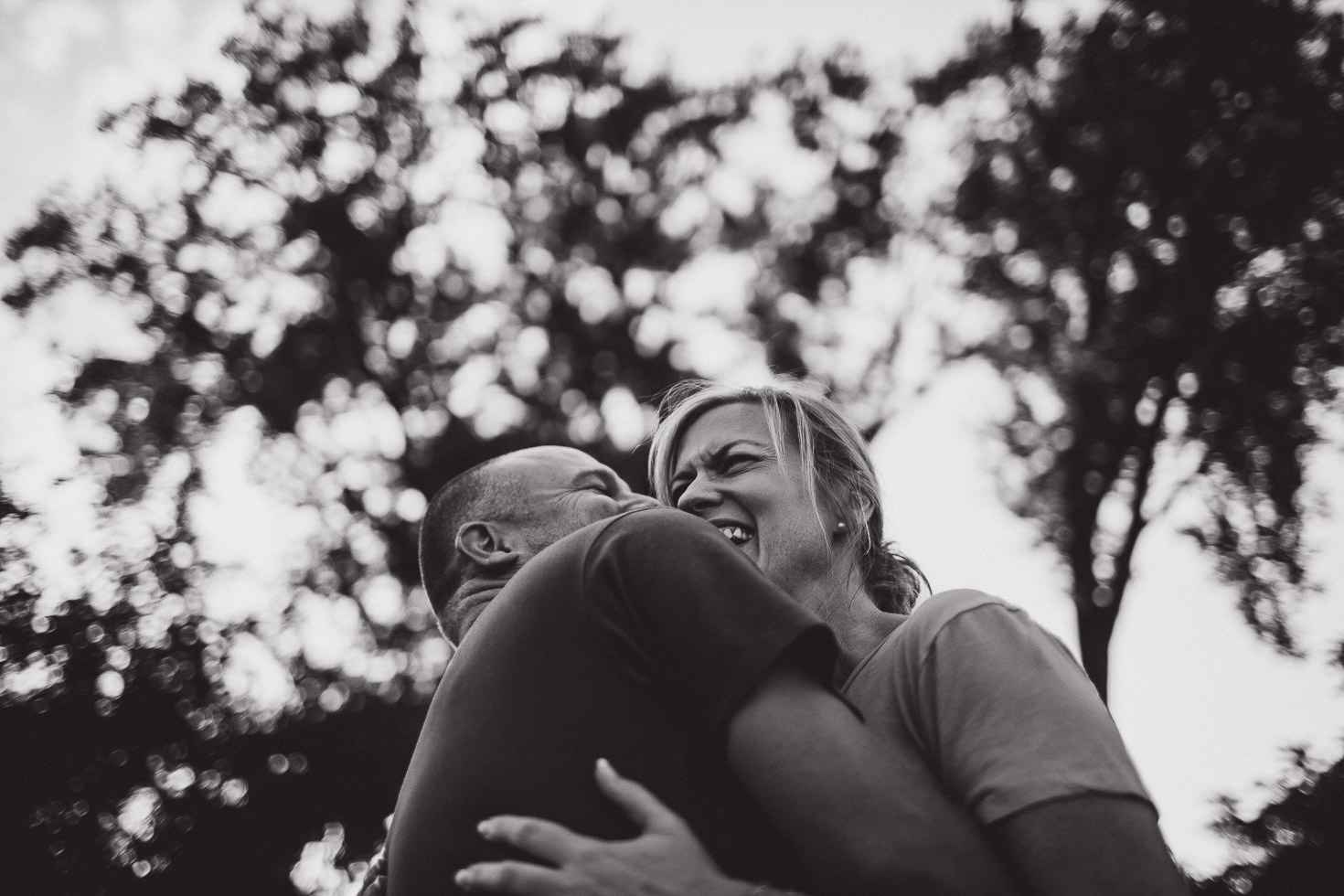 Couple embracing in laughter, wide angle image shot from below, black and white