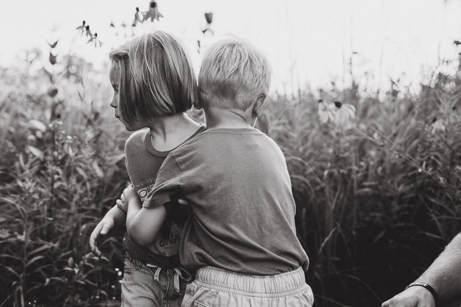 brother and sister hugging in field