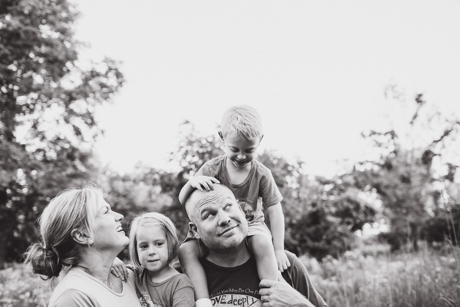 Portrait of family in open field, black and white, son sitting on father's shoulders
