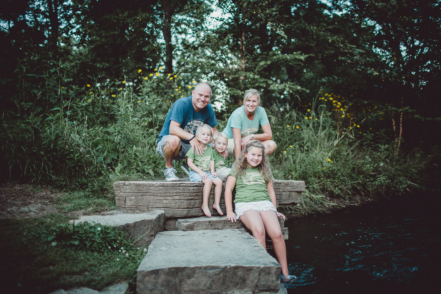 smiling family portrait beside creek