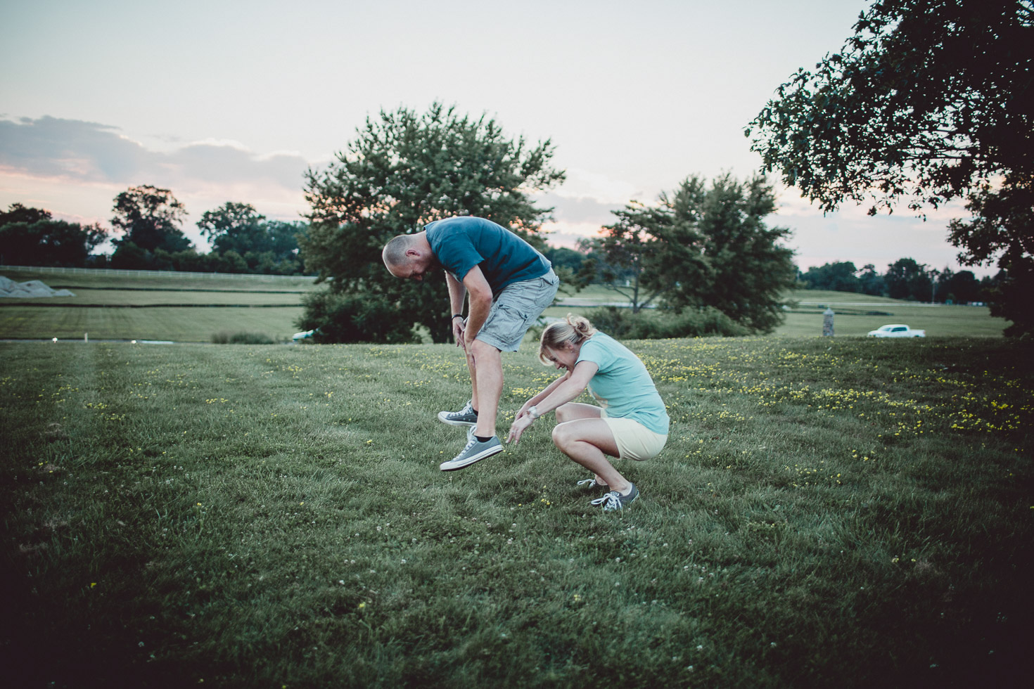 couple playing leapfrog in field