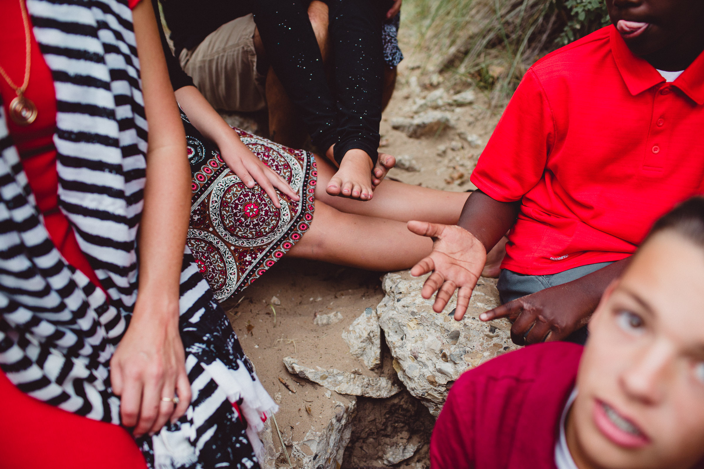 details of hands and feet of family in the woods telling stories