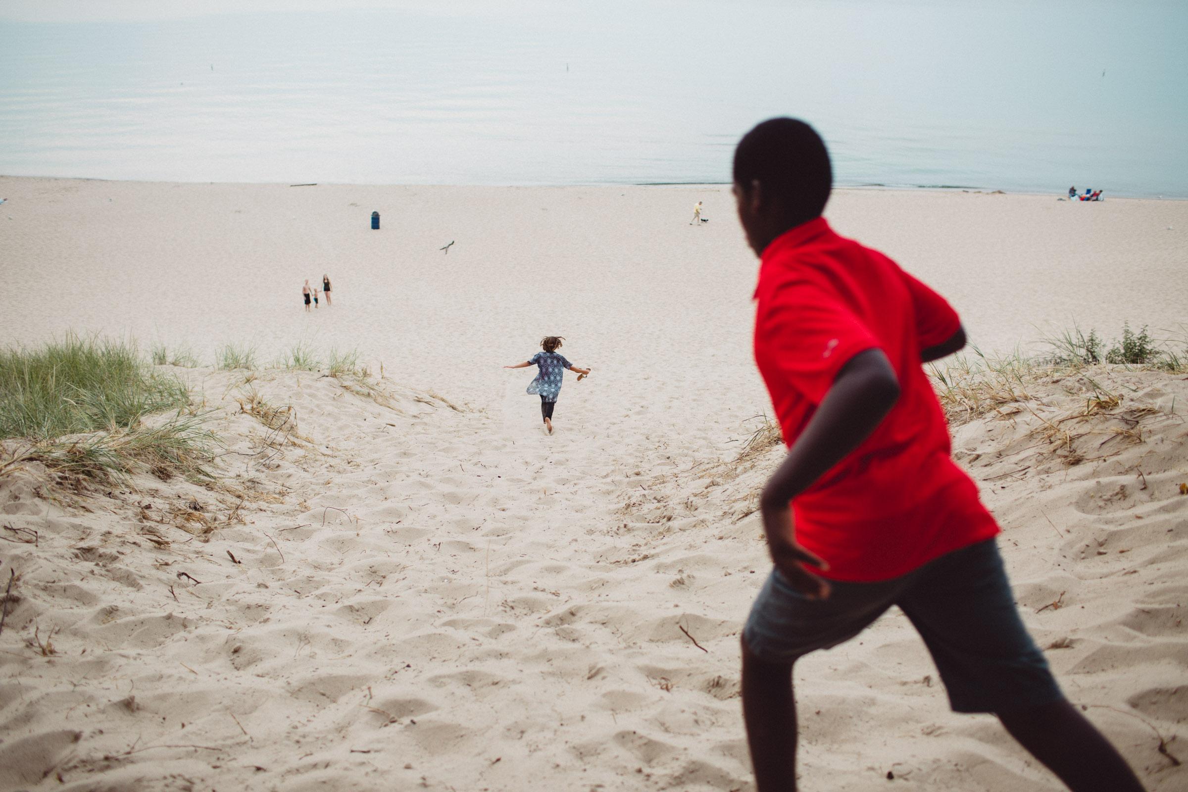 children running down sand hill