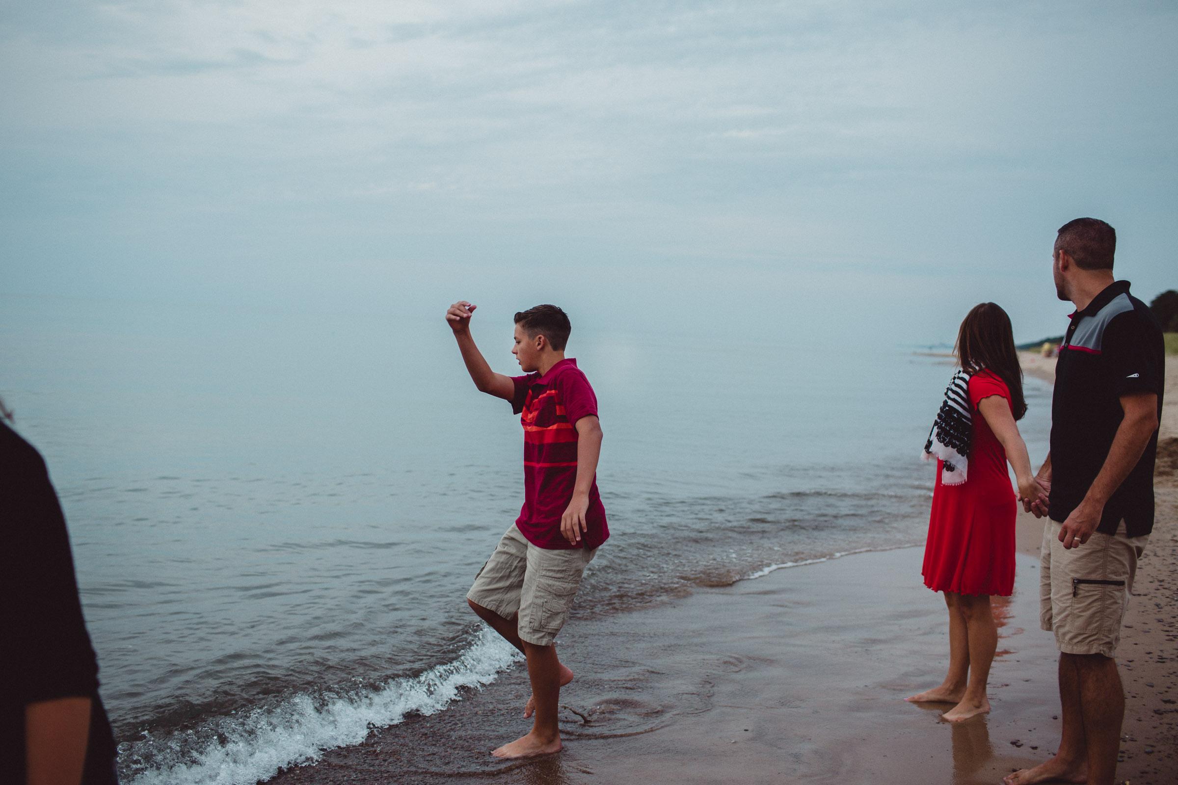 teenager throwing rocks into the lake