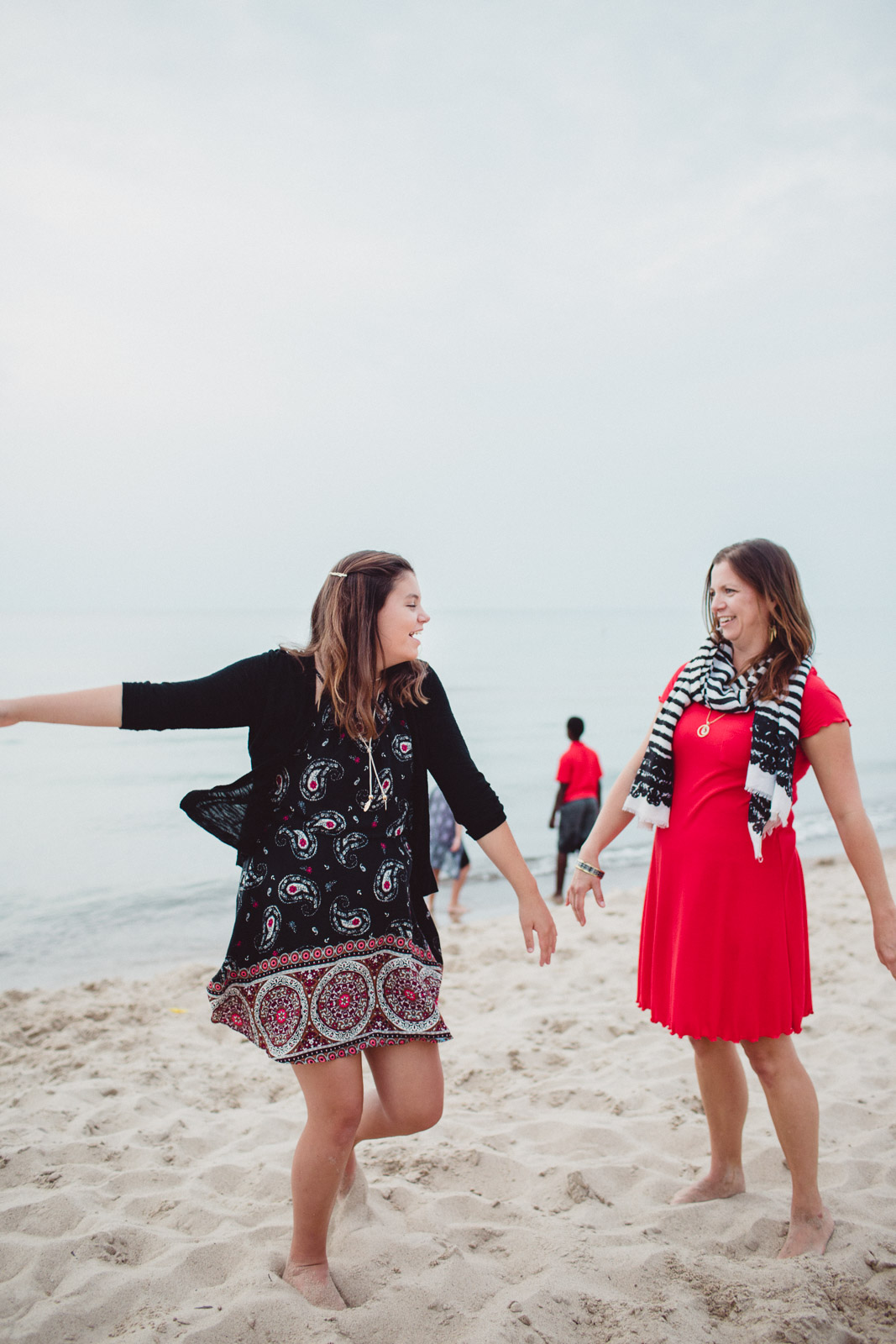a mother and daughter dancing together on the beach