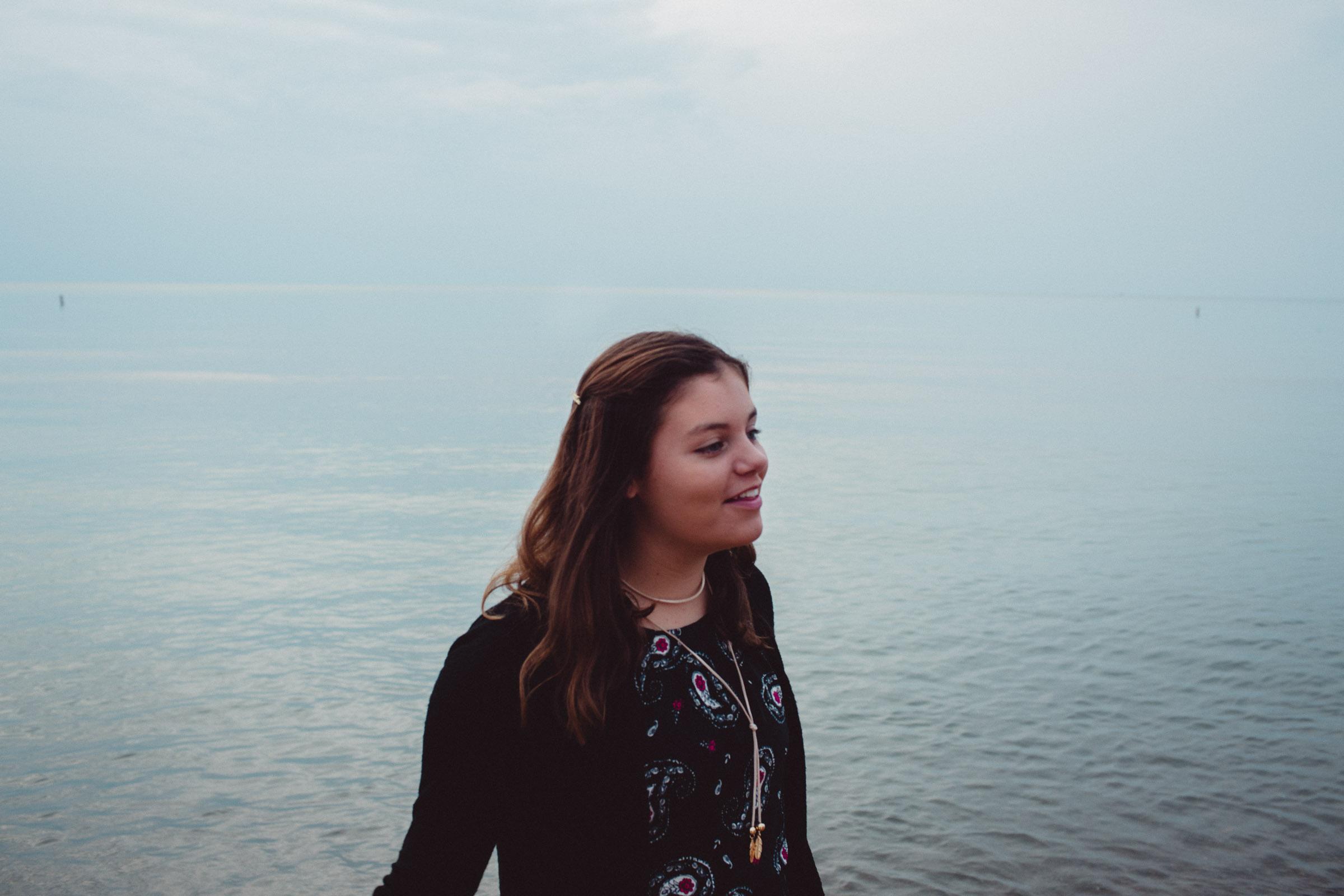 girl walking along the water