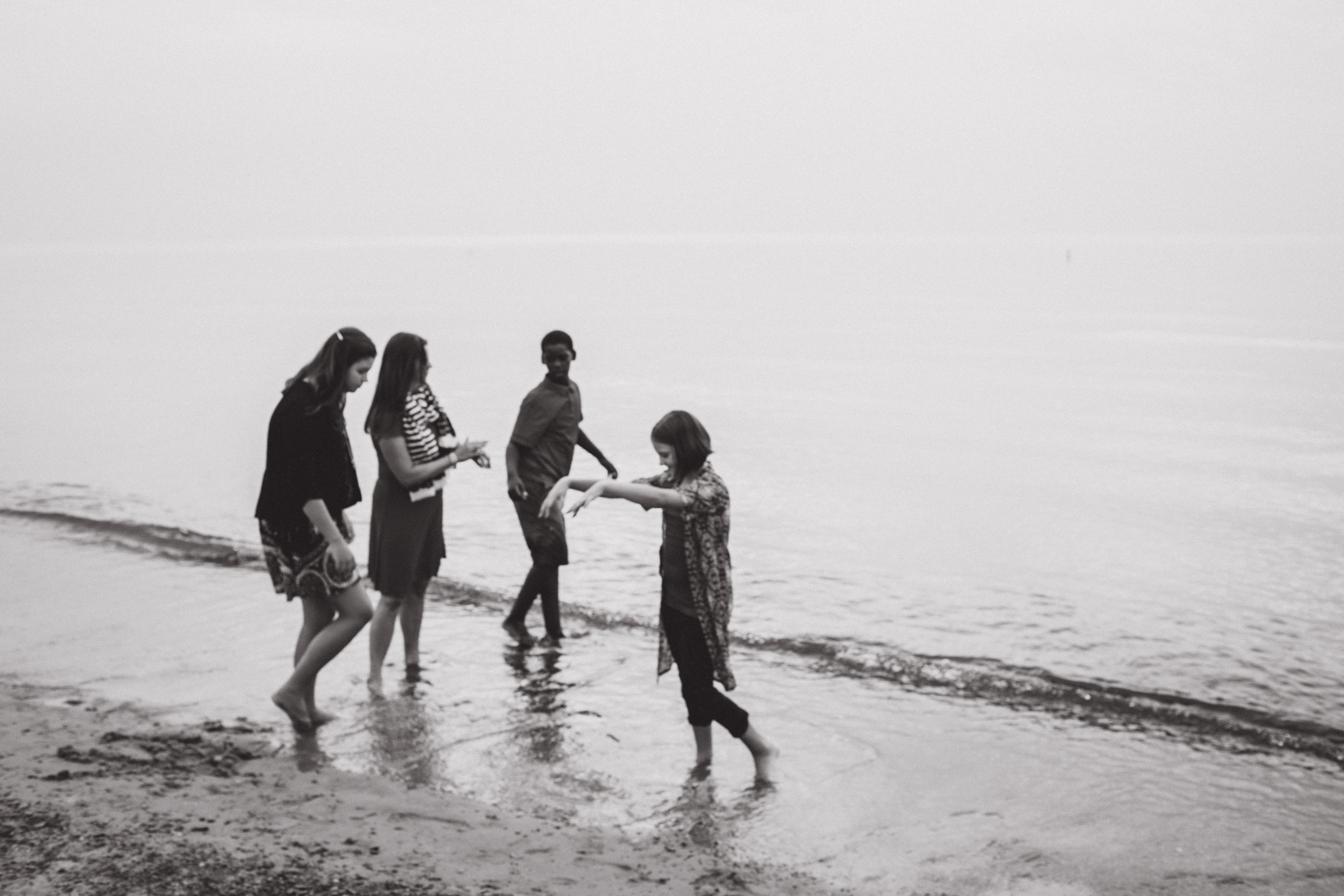 children dancing by the water, black and white