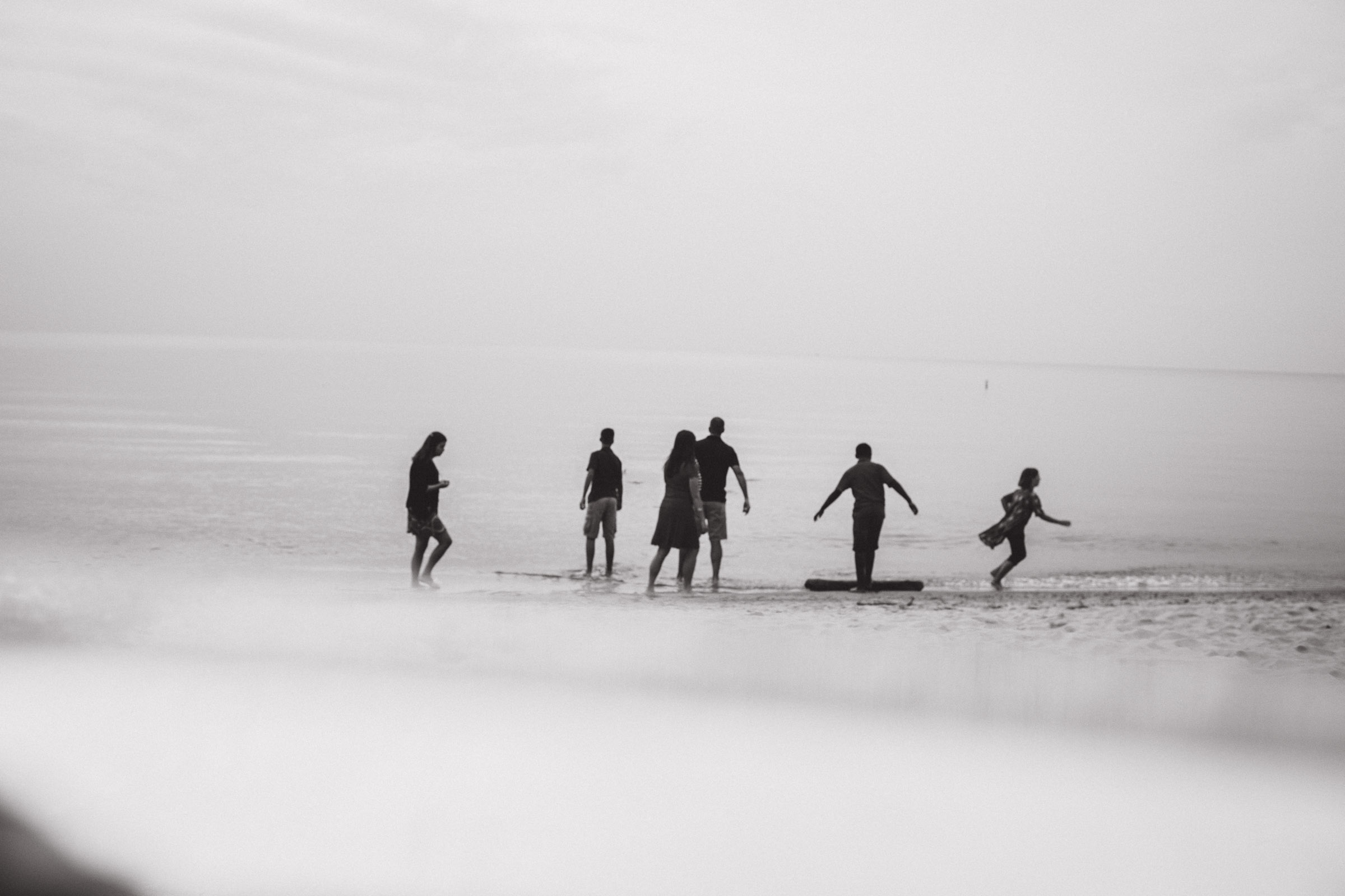 family connecting and playing by the water, black and white